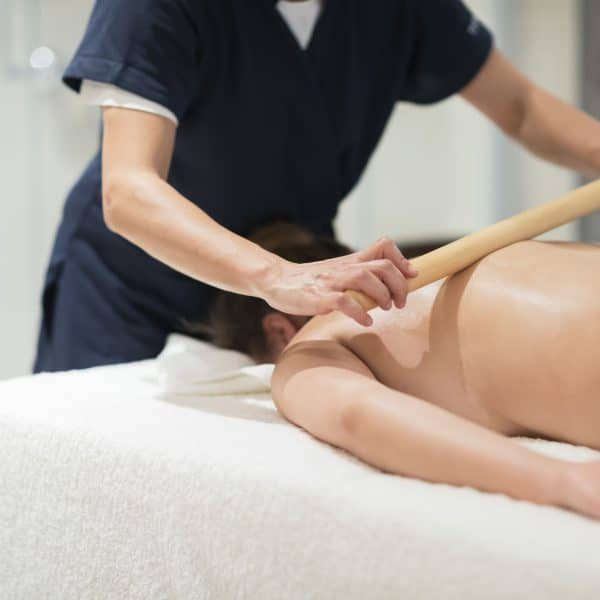 Masseur using massage bamboo sticks during treatment
